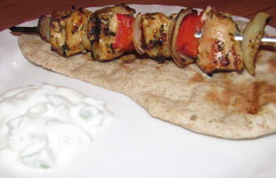 Grilled Chicken Shish Kebab Served On A Freshly Made Chapati With A Cucumber Raita Side
