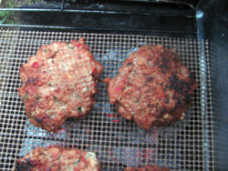grilled venison burgers over charcoal