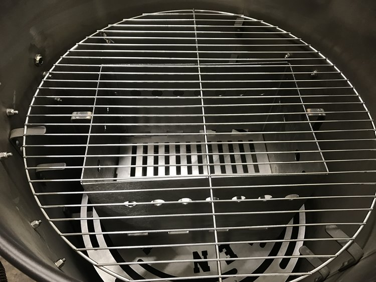 Place the fire basket on the heat deflector plate to grill in the Ultimate Drum Smoker